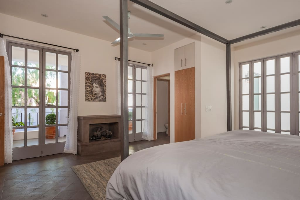 Master Bedroom with stone fireplace and ensuite bathroom and doors to balcony