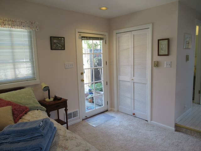 Entrance door and clothes closet on right with full sized ironing board, iron, and space for your clothes.