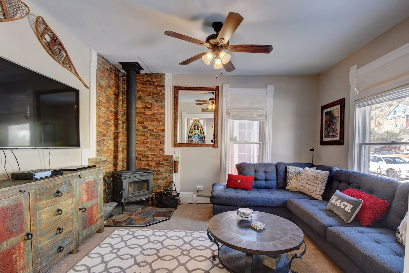Family Room with wood burning stove. Large couch to enjoy the fire and watch TV.