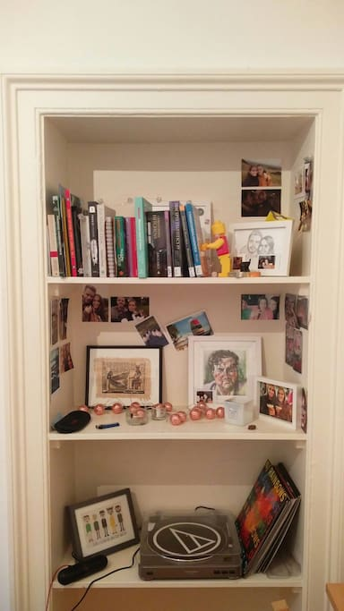 Our book shelf; showing some homemade art, interesting reads and personal photographs