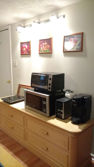Kitchenette: small fridge,  Induction Cooktop, mircowave, toaster oven, Keurig with flavored pods.  Includes dishes, pots, utensils... pantry drawer....