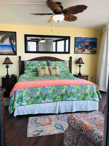 Caribbean theme master bedroom has king size bed with soft topper on mattress & Tommy Bahama bedding. Freshly painted and new flooring!