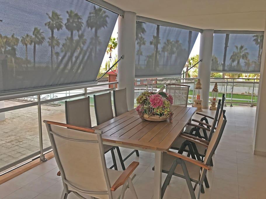 Amplia terraza con zona de sofás y televisión y otra zona con mesa para comer.