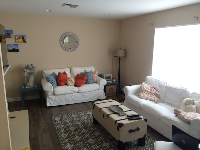 """Bright open space living room with fire place and 65"""" wall mounted TV."""