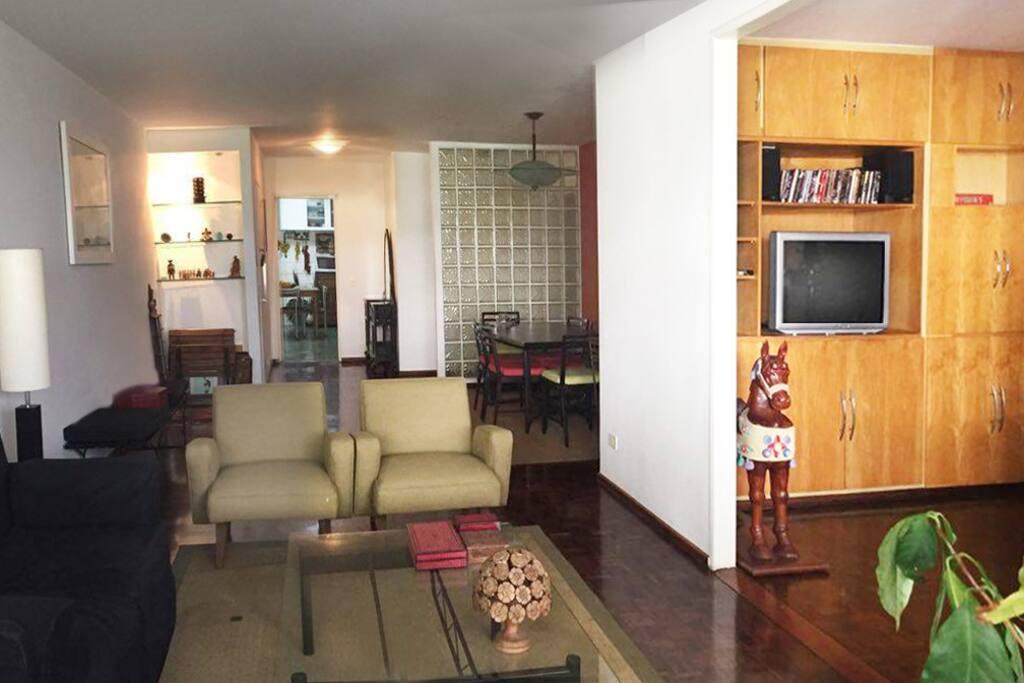 ambiente claro e harmonizado, salas e cozinha ao fundo