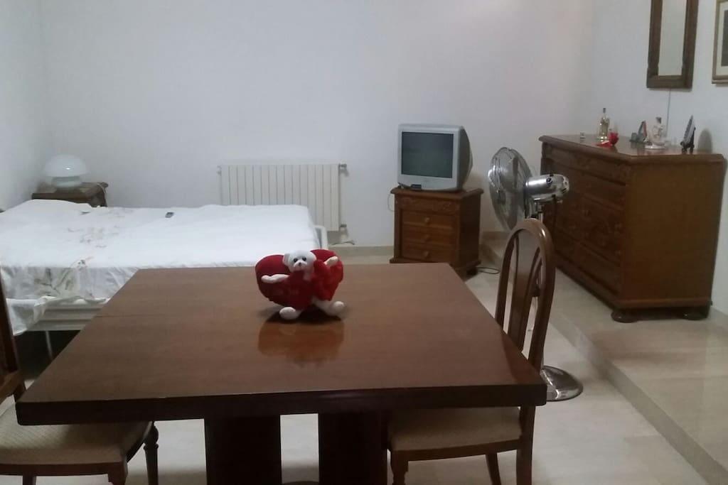 Camera dotata di tv letto tavolo e uno spazio nell'armadio