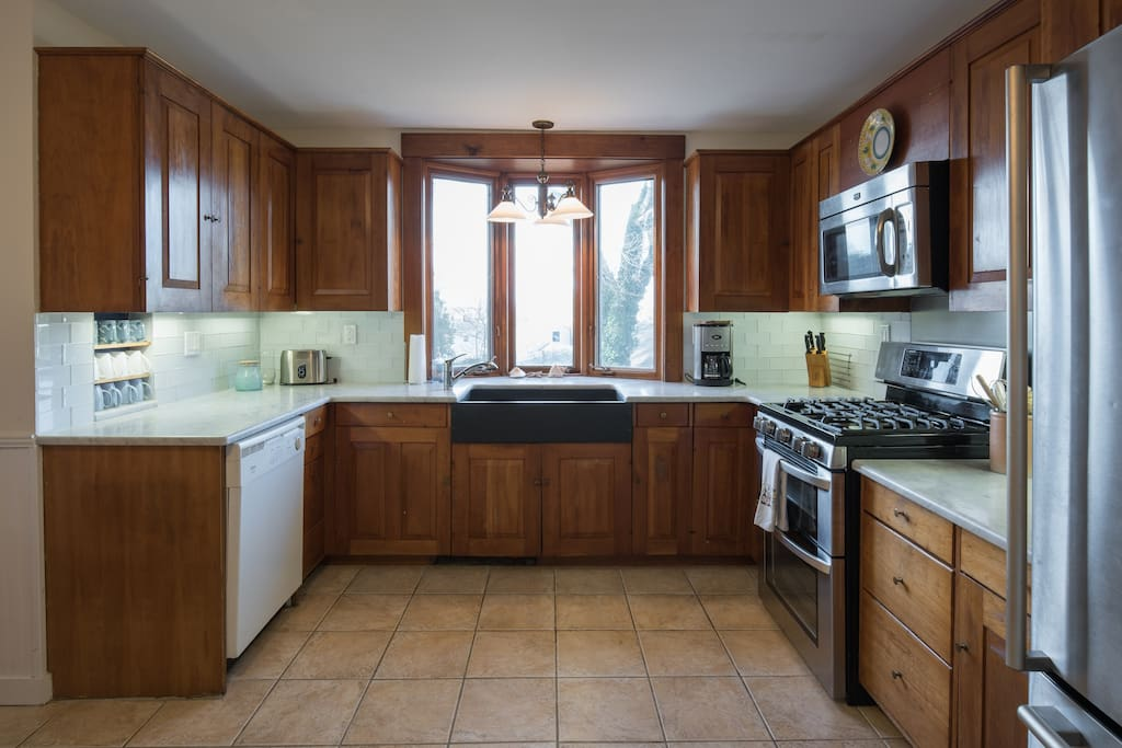 Spacious kitchen with farmhouse soapstone sink and marble countertops.  Gas range.