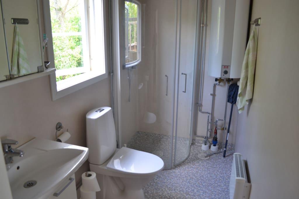 Toaletten finns i gråa huset