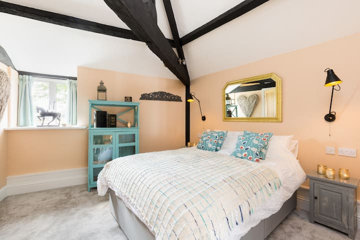 The Pool Side en suite bedroom with a luxury kingsize bed and exposed original beams.