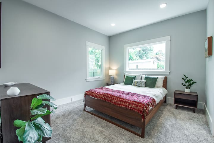 """Private bedroom with great lighting, extremely comfortable bed, dresser, nightstands, 55"""" TV, and attached en suite bathroom. Closet contains ironing board + iron, hair dryer,  hair straightener, and extra blankets/pillows."""