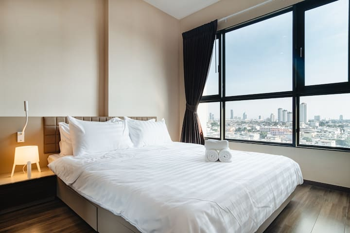 Comfortable bed and pillows with fresh bedsheet and towels.