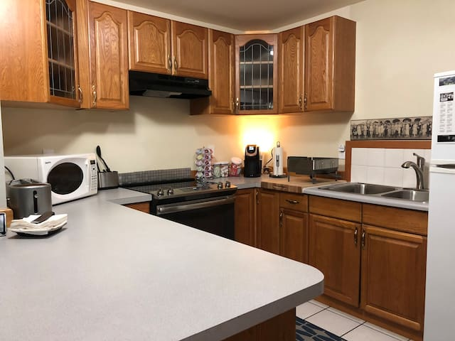 Kitchen with stove, microwave, toaster, coffee maker, refrigerator, dishes, utensils, pots, and pans.