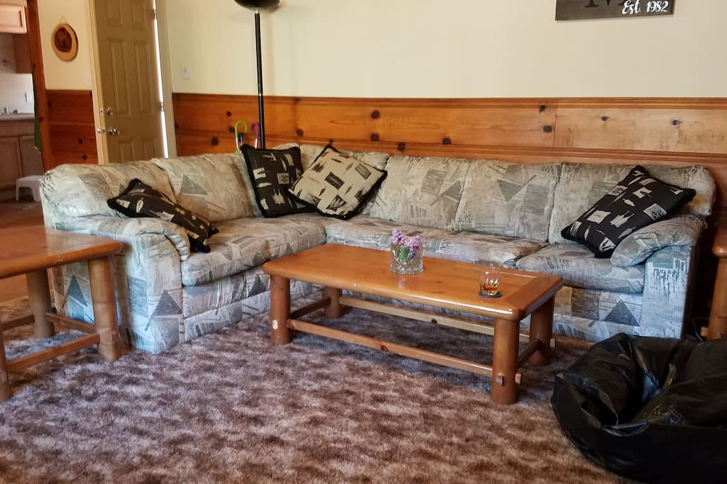 The living room has comfortable couch and a couple of bean bags for lounging around in front of the fireplace.