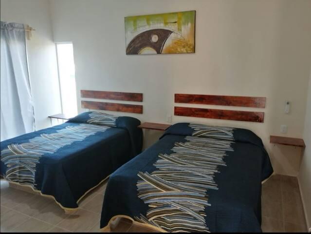 Habitación 1 con 2 camas matrimoniales, climatizada y clóset. Con acceso a un baño desde la habitación. Desde el balcón podrás disfrutar de un bella vista a la playa.