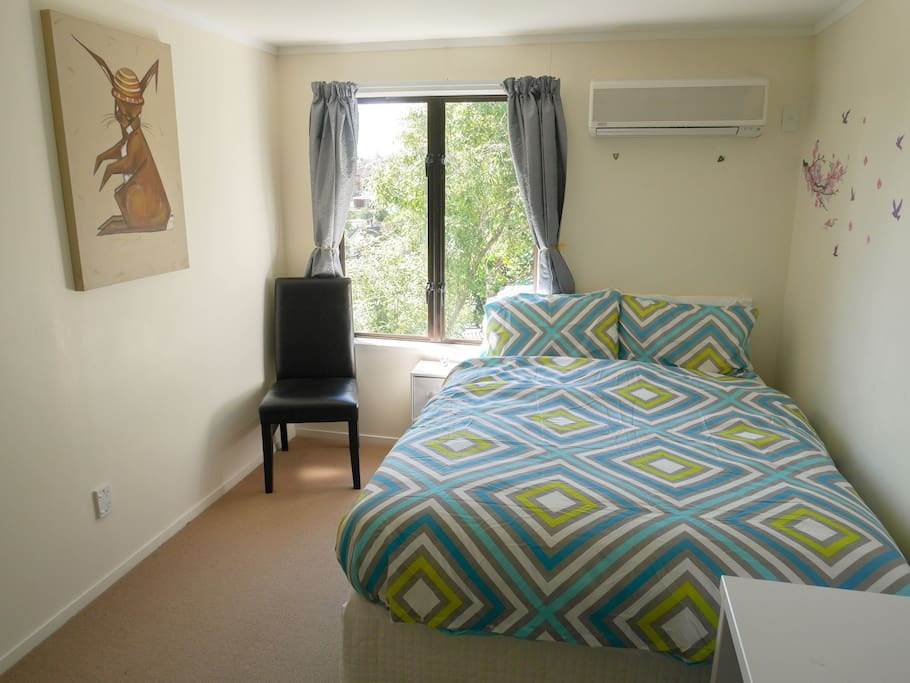 Bedroom includes comfy double bed with dual control heating blanket, desk with mirror hanging above, additional full length mirror, nice view with lots of sun, air conditioning/heatpump, and lots of closet space.