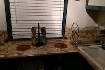Dish drainer sits next to the deep sink on a counter top made from excess tiles.