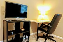 Bedroom is furnished with a 32-inch flat screen TV equipped with cable channels and a desk