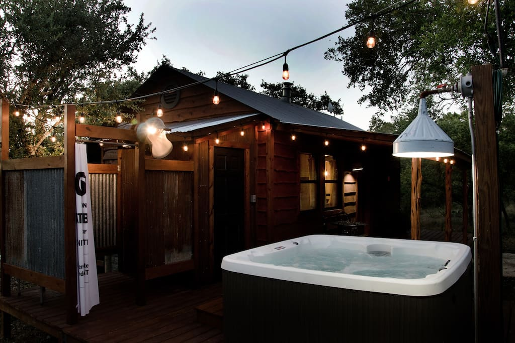The back of the cabin features the hot tub and outdoor shower