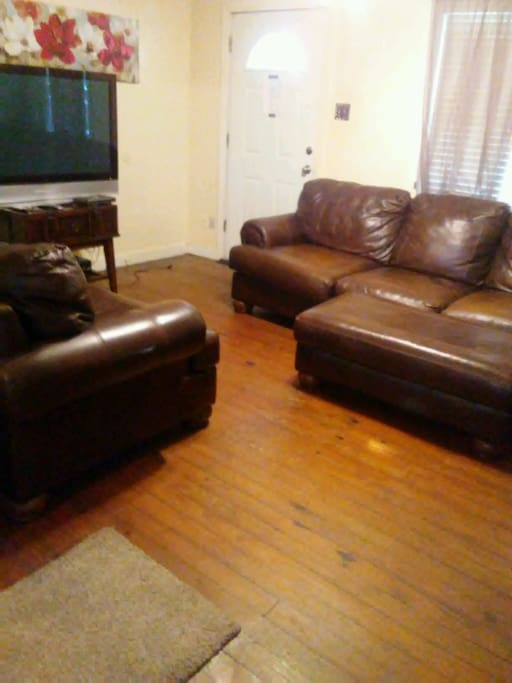 "Living room with nice leather couches and 55"" TV."