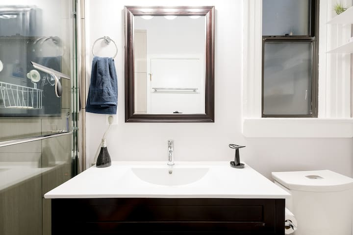 Sink and mirror in shared bathroom.