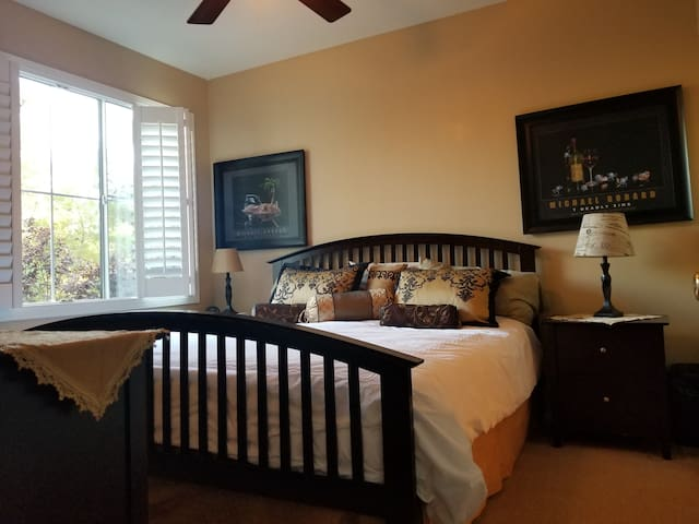 King size Sleep Number bed in Master bedroom with generous space on either side.   Black, gold and white decor.