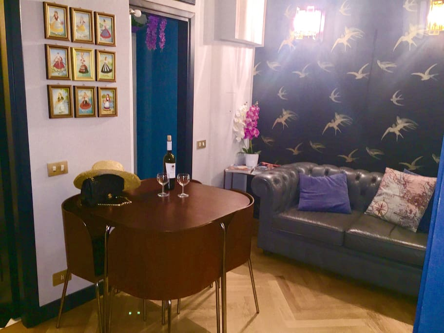 entrance and little living room with sofà and table for dinner