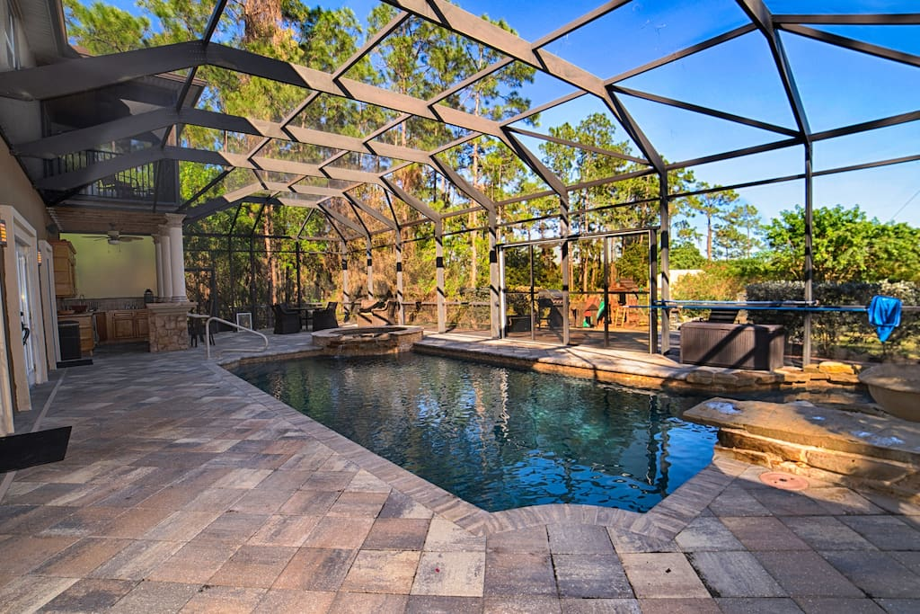 Salt Water heated Pool, with Natural Rock jumping Board, 3 bar stools lay under water right below the Spa waterfall.