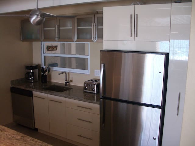 New kitchen with large Stainless fridge whirlpool dishwasher and granite countertop