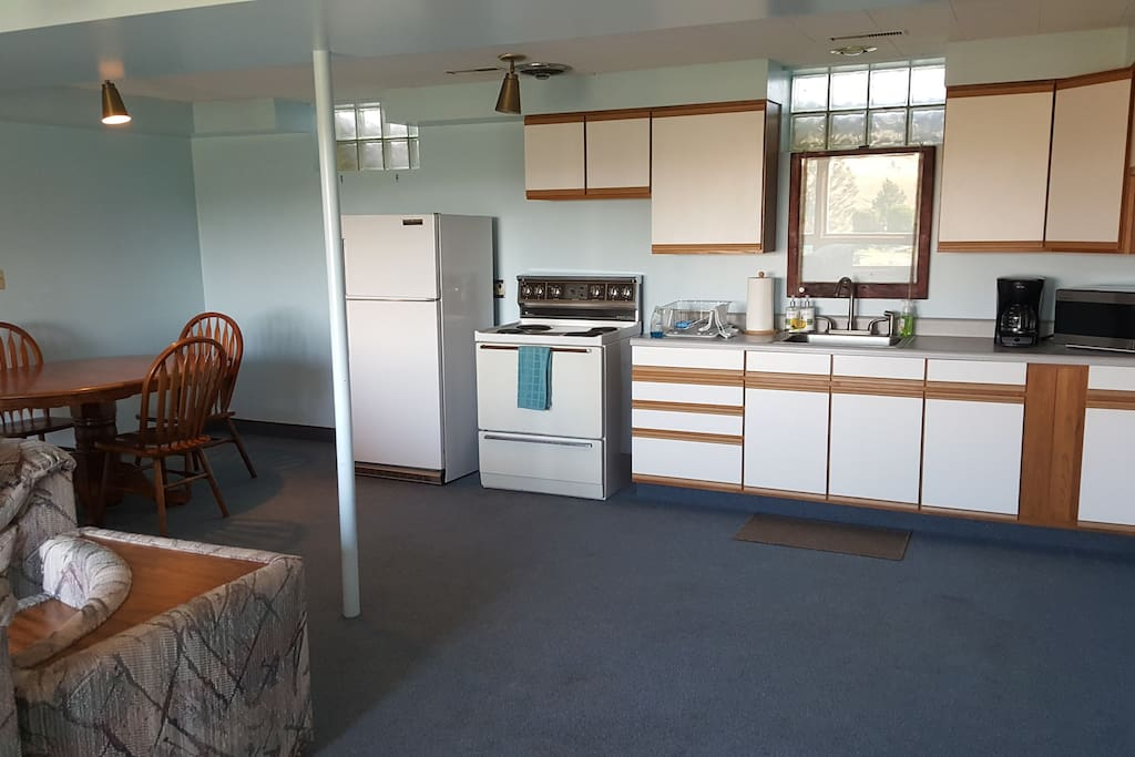 Kitchen equipped with cooking utensils, dishes, and silverware.