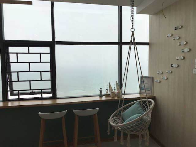 Hanging chair and minibar by the window with impressive sea view