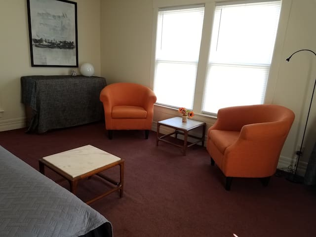 Livingroom area with a single bed chairs, built in book case, ceiling fan, ac,dresser, veiw of Woodburn hall, short walk to downtown Morgantown,WVU campus, Prt station,  rails for trails, Amphitheater and more! On bus lines short drive to everything
