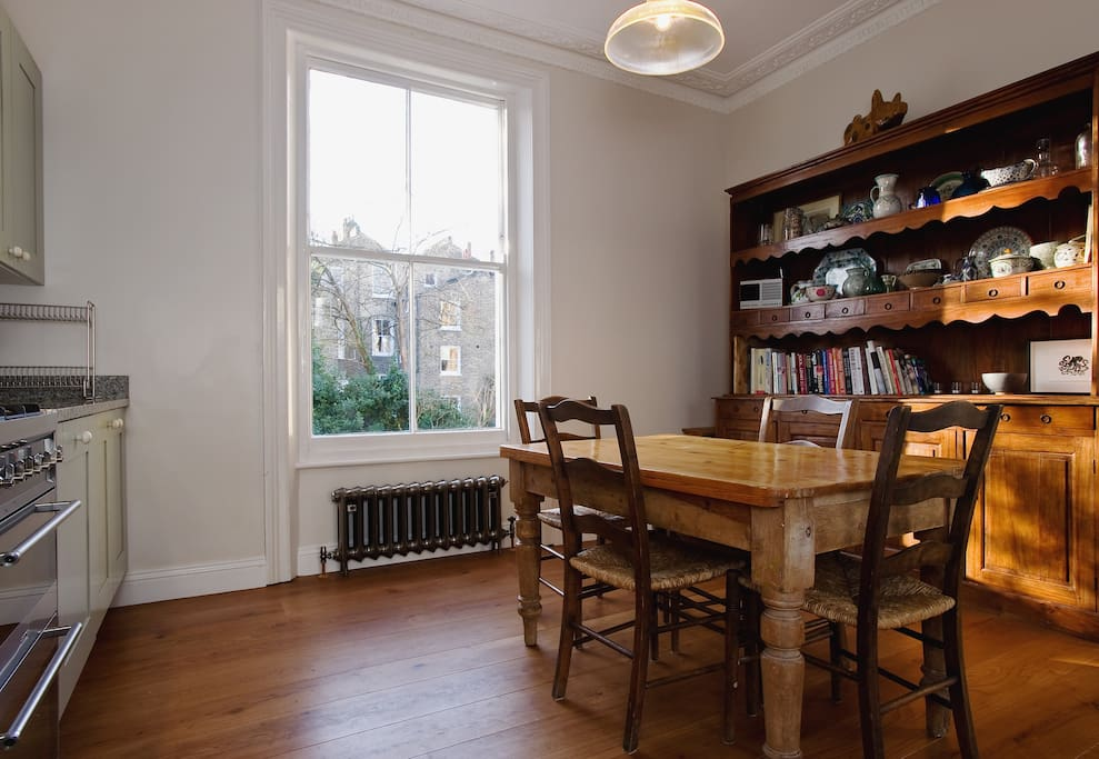 Dining table in the kitchen with a large south facing window overlooking the garden