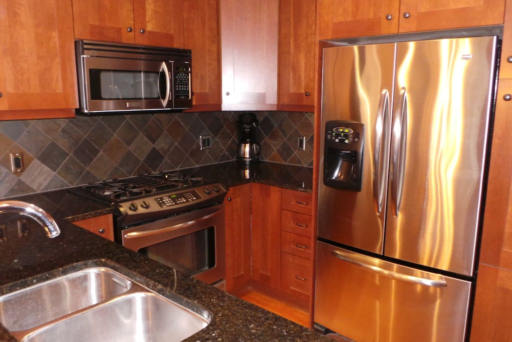 Granite, stainless steel appliances in well equipped kitchen.