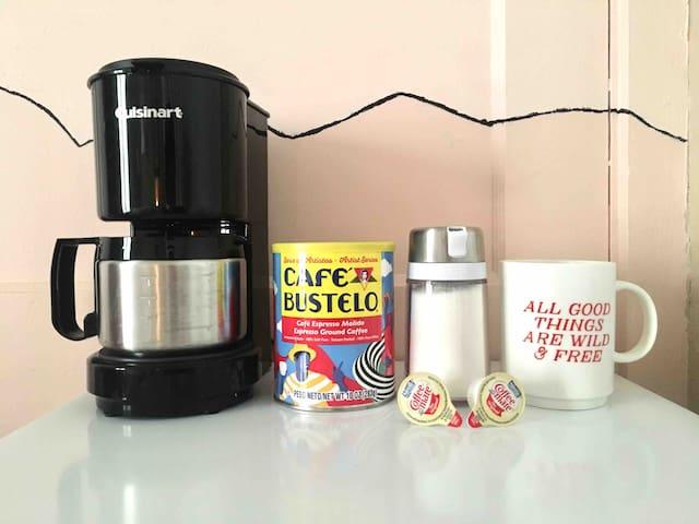 Mini fridge, coffee maker, coffee, sugar, and cream.