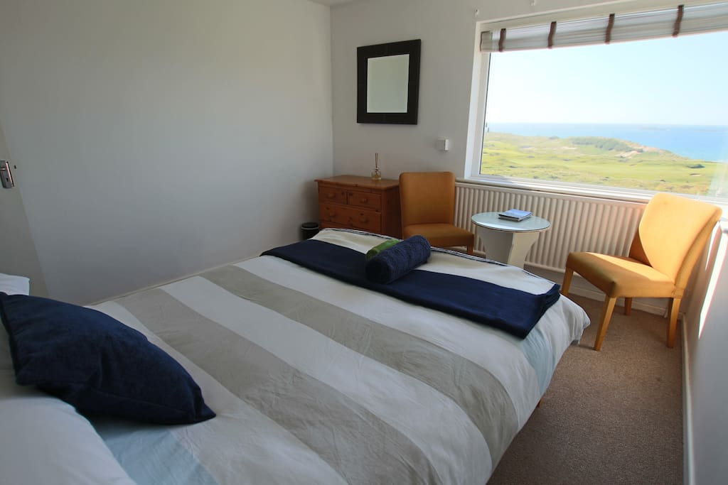 Cosy bedroom with stunning views over Royal Portrush Golf Club and the North Antrim Coast.