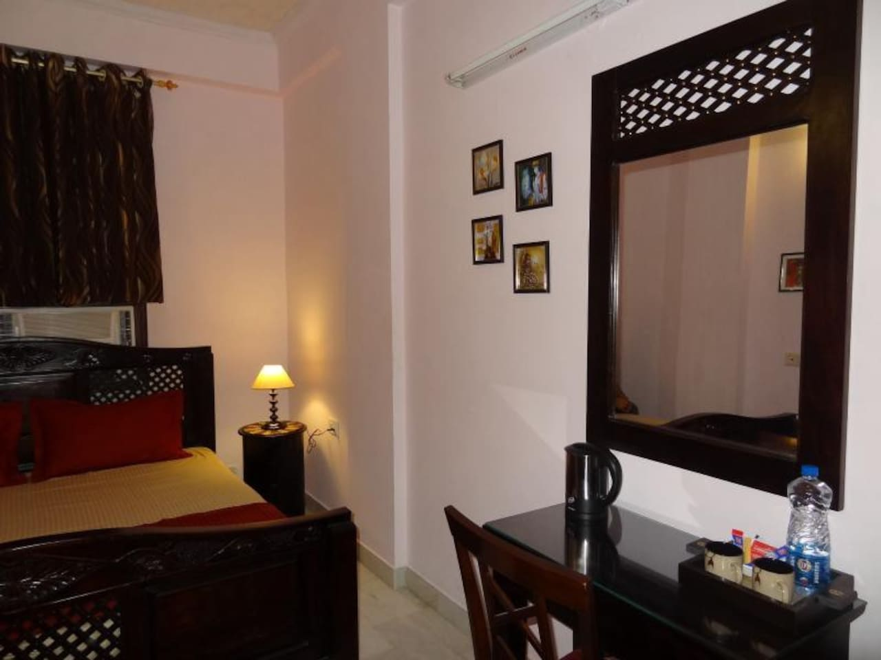 Master Bedroom with carved traditional solid wood large bed, air-conditioning, writing desk and vanity mirror, tea-coffee maker, wardrobe, safe and attached bathroom