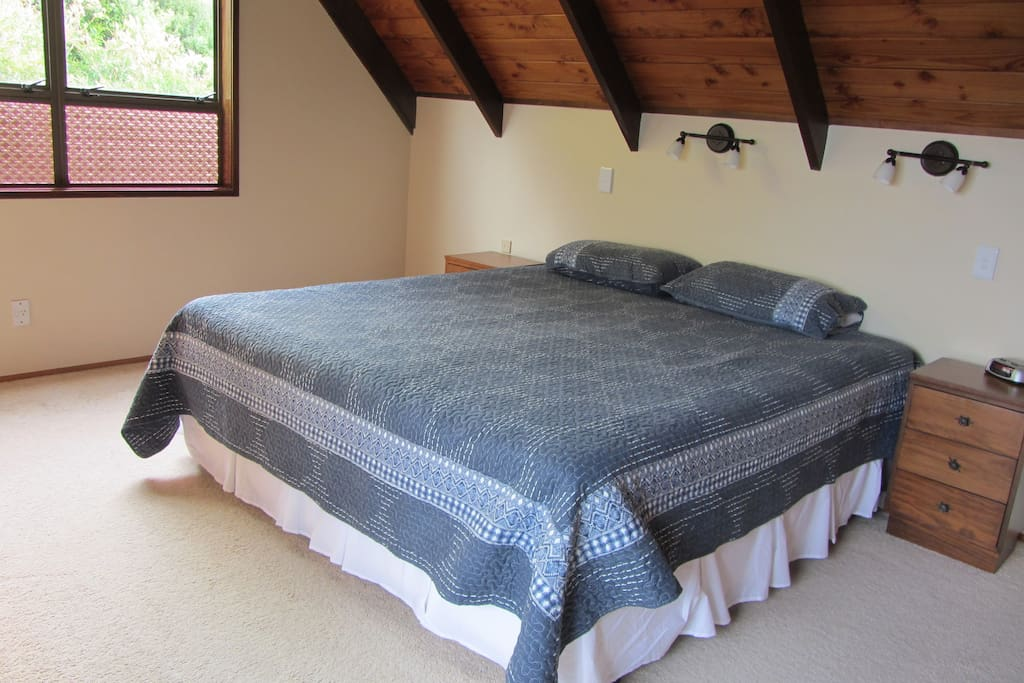 Master bedroom with en-suite on top floor. Twin single beds zipped together to make a super-king. Views to Great Barrier from bedroom and adjoining lounge windows.