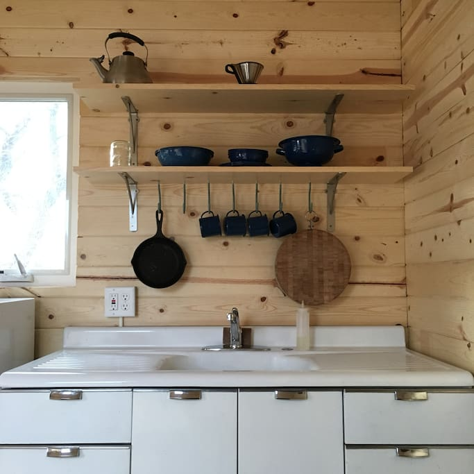 The cabin kitchenette includes a sink with hot water, a mini fridge, and an electric hot plate.