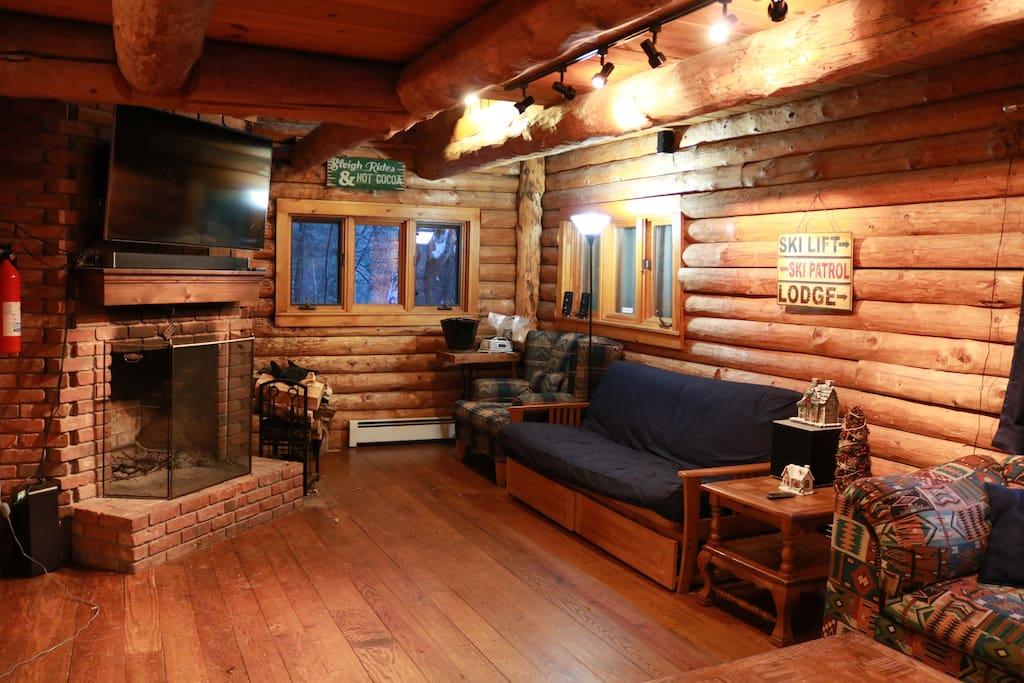 Open living room with wood burning fireplace and DIRECTV