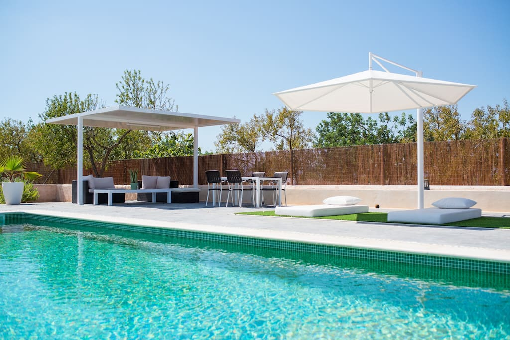 Pool with sun beds, comfortable day beds with shade, sofa corner and table and chairs