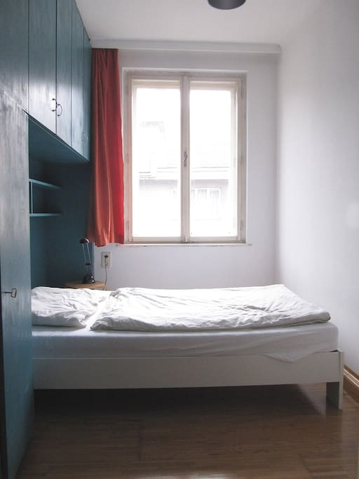 The bedroom has one window as well as a wall unit with shelves providing a lot of storage space.