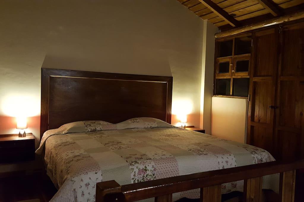 Habitación. Cuenta con una cama de tres plazas (king size) y acceso al balcon. Los materiales usados en la construcción hacen q sra fresca de dia y calida en la noche