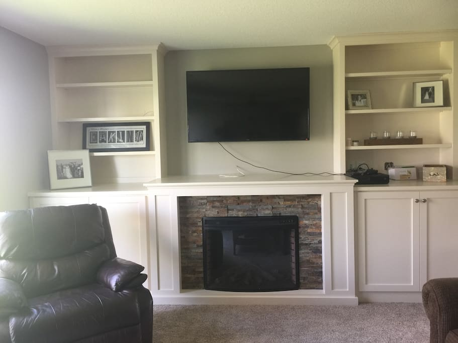 Downstairs living room, featuring entertainment center and fireplace