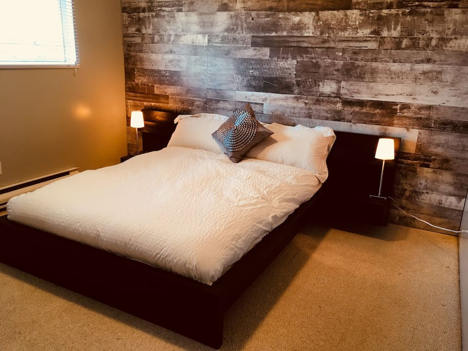 Bedroom 1: Modern comfortable queen-size bed with a down comforter.