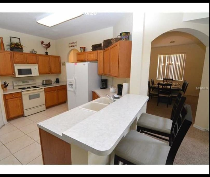 Spacious fully stocked kitchen with breakfast bar