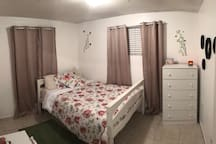 Cozy room with a full bed, closet, ceiling fan & light, dresser and small table & chair.