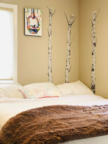 Our light and airy east bedroom with a queen bed and an assortment of pillows to ensure a comfortable night's sleep.