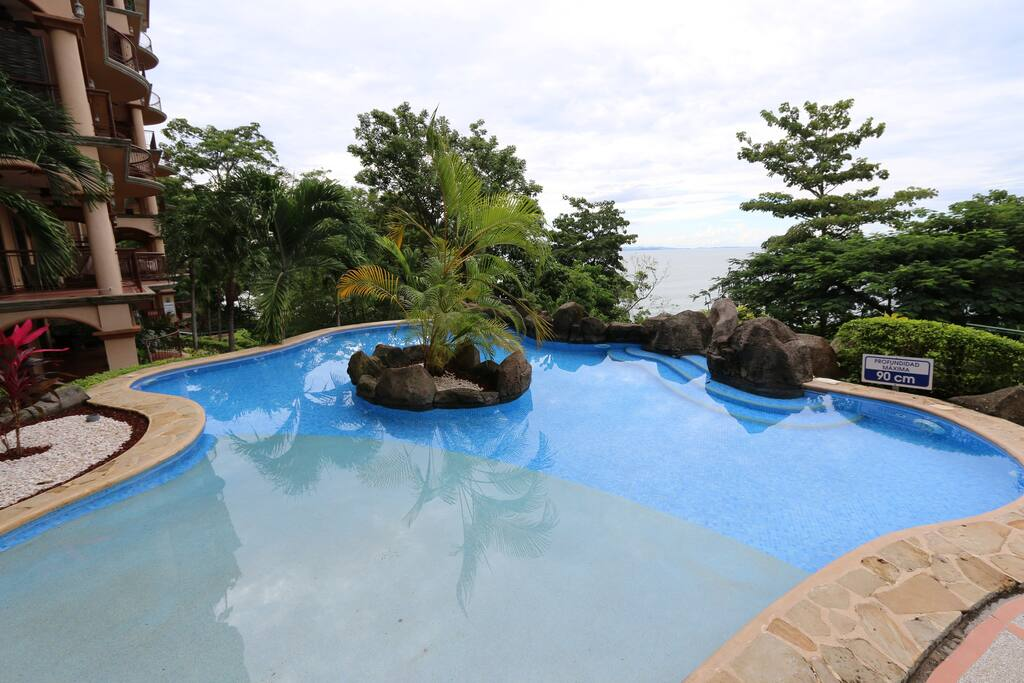 The upper pool is shallow with a sloped entry and view of the ocean.