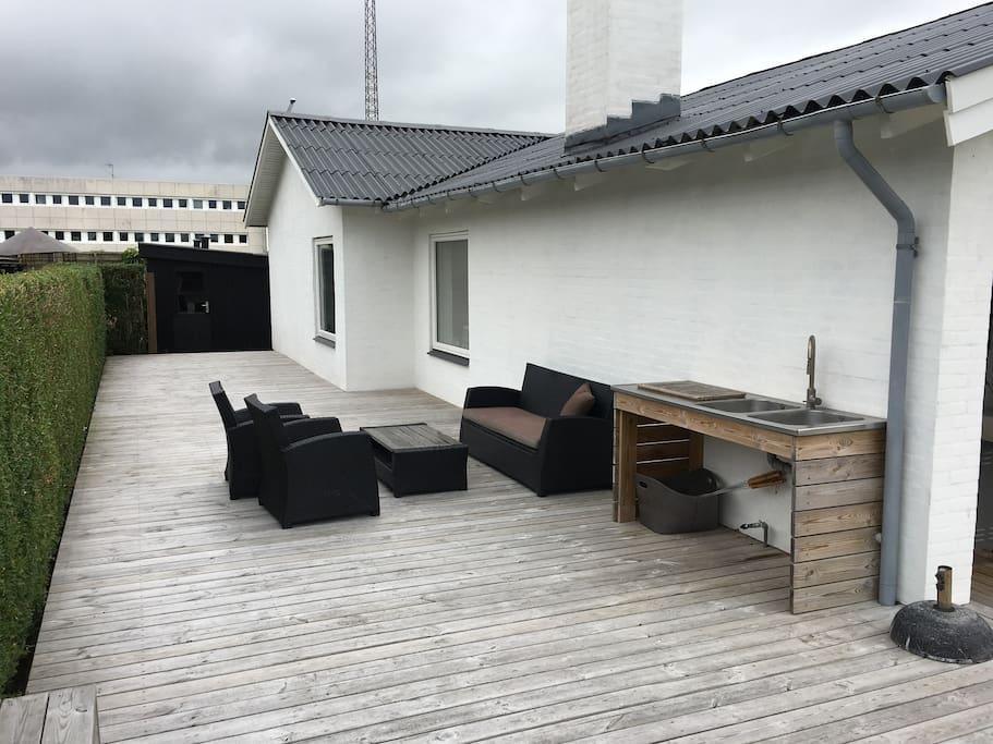Terrasse på siden af hus med udekøkken