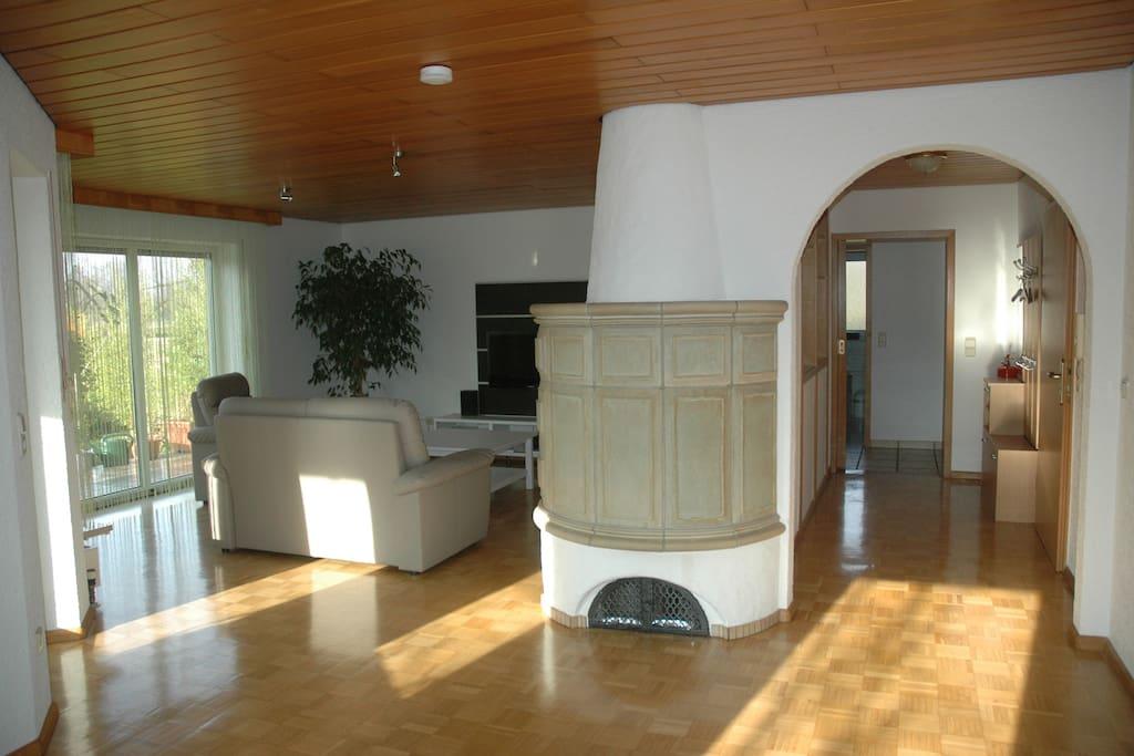 großes offenes Wohnzimmer mit Kachelofen und zugang zur Terasse und Wintergarten